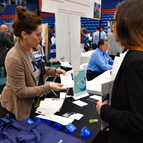 Image of an employer at the UNH Career Fair reviewing materials with a student