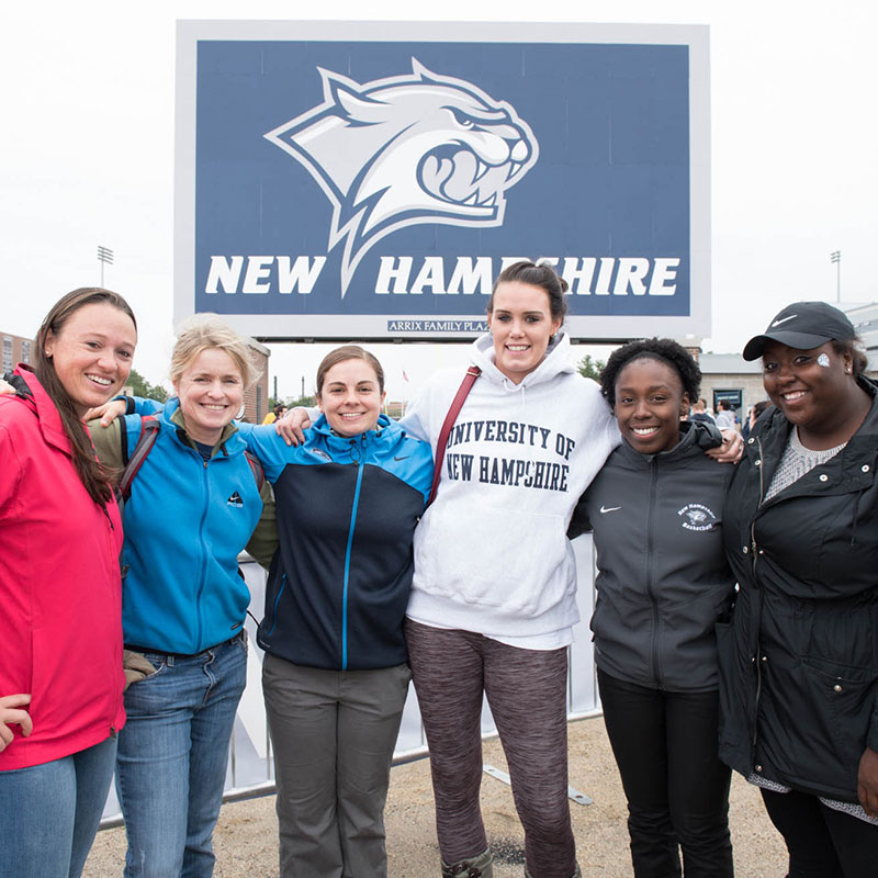 Six UNH alums pose for a picture in front of the Wildcat sign at Wildcat Stadium
