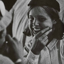 Old photo of female student smiling in a hat