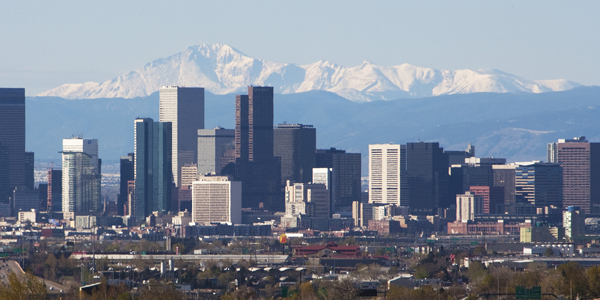 Daytime photo of Denver skyline with mountains in the background.