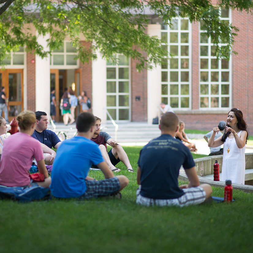 UNH students sitting on the grass receiving an outdoor lecture in the Murkland Courtyard