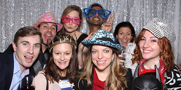 Photo of 8 UNH alumni smiling for the camera at the New York celebration with sparkling background.