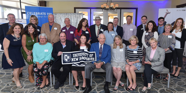 UNH Alumni gathered at the C150 event in Southeast Florida holding a UNH banner.