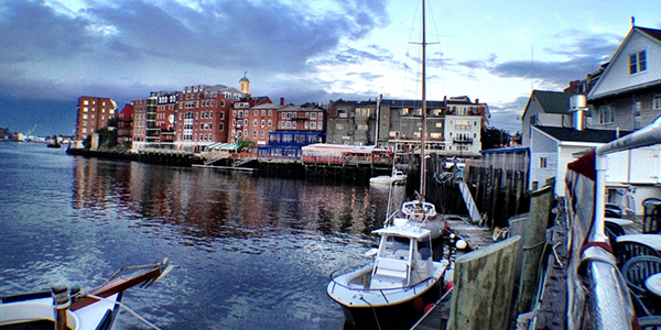 Daytime photo of harbor area on the seacoast of New Hampshire with boats and buildings in the background.