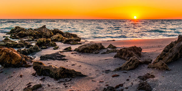 Sunset photo of Florida beach with rocks and waves