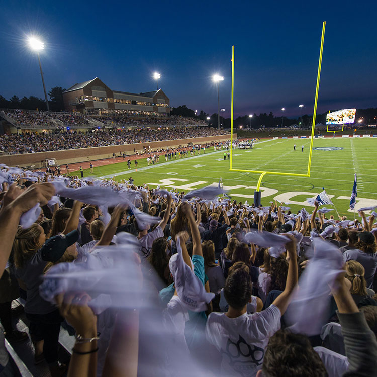 Fans cheering in the end zone of the UNH football stadium