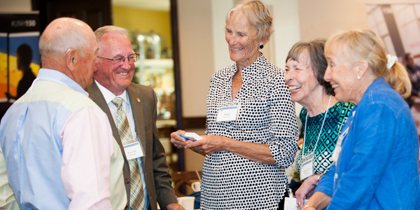 UNH Alumni gathered at C150 event in Southwest Florida, talking and laughing.