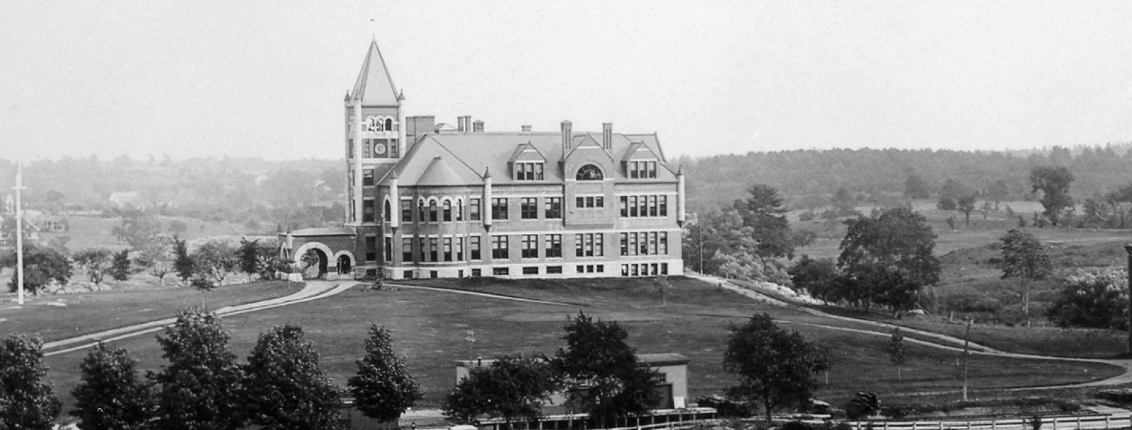Old photo of Thompson Hall with trees and fields in the foreground