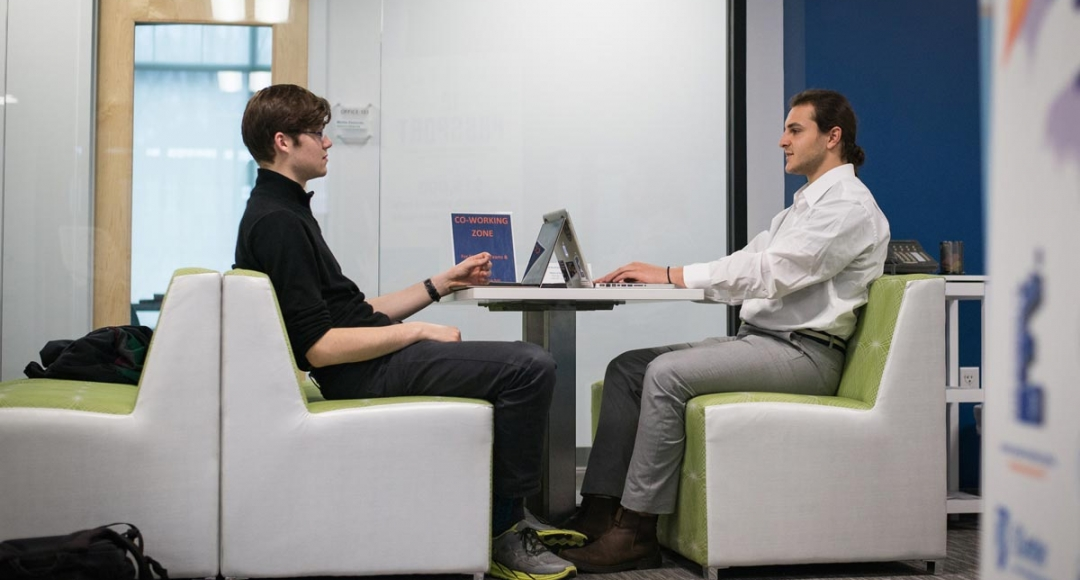 Two male students sitting at table with laptops