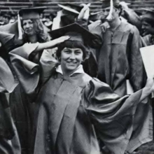 Old photo of a female student in cap and gown holding diploma