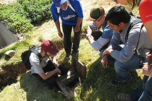 In San Pedro De Casta, Peru, UNH-Students Without Borders members examine the water distribution box and piping system