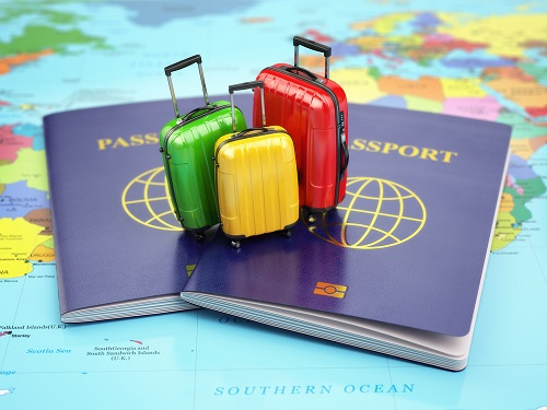 mini suitcases on passport on map of world (photo purchased from Shutterstock)