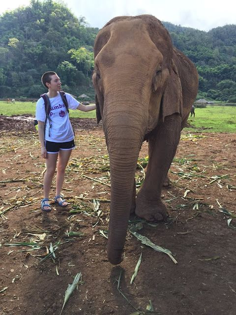 Margo Clark in Thailand standing next to an elephant