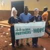 (l. to r.) Elizabeth Lapsley, Aboubacar Konate, and Kiley McKenna holding GiPH banner