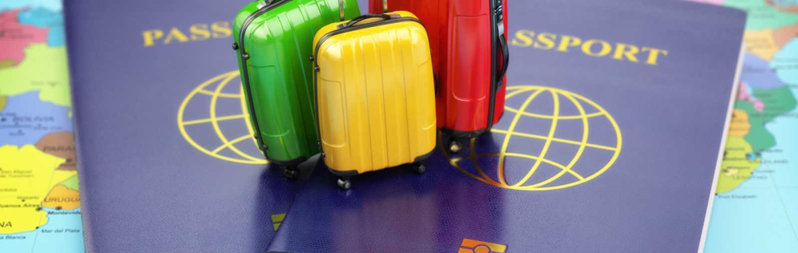 photo of mini suitcases and passports on world map