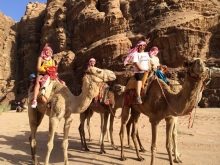 Photo of students  on camels in desert