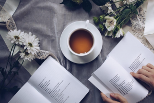 Cup of tea laid out on a table with books and flowers