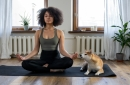 woman meditating at home next to her dog