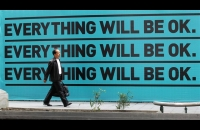 "Man walking in front of a sign reading ""everything will be ok"""