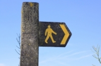 picture of a wooden sign attached to a post with a yellow figure of a person walking and a yellow arrow pointing to the right.