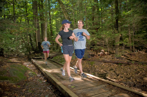 a couple jogging through College Woods.