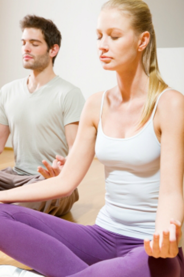 image of a man and woman in yoga style clothes seated in meditation pose.