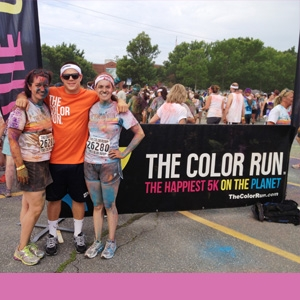 amy schwartz and two adults pictured at an outdoor running event in the summer time.