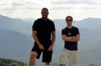 two men outdoors posing on top of a mountain in the summer time.