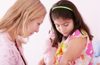 a female doctor administering a shot to a young girl in a floral dress and pink head band.