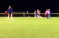 students on an athletic field playing soccer at night under the lights.