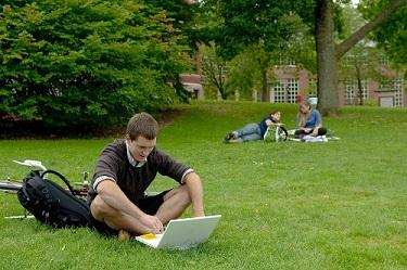 student working on laptop on t-hall lawn