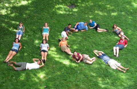 students laying on lawn in the shape of the letters u and q