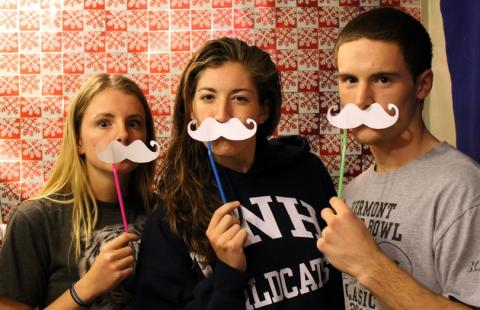 students holding up fake mustaches