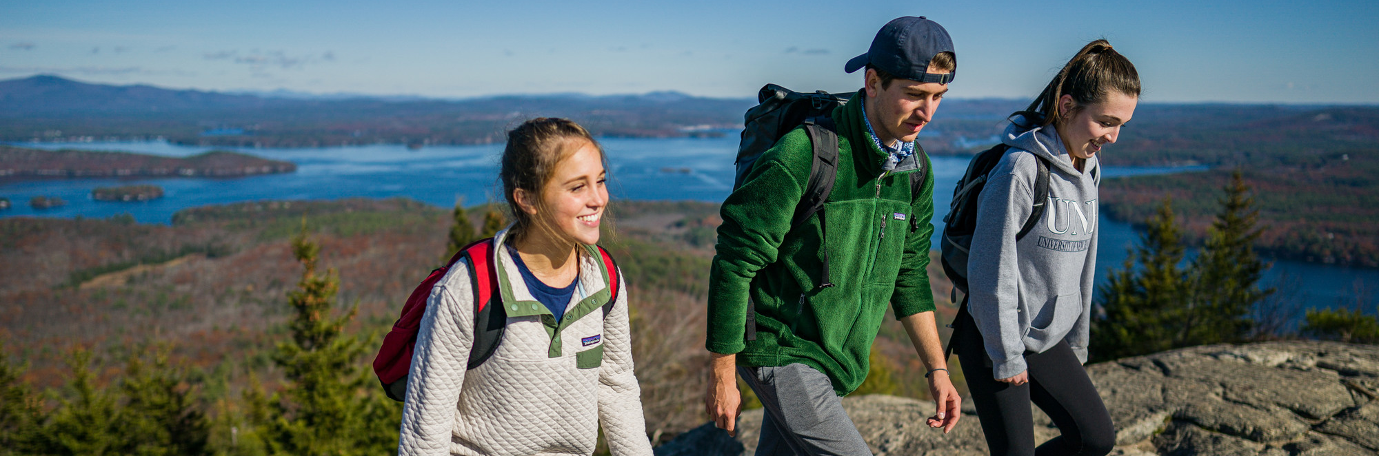 Three students walking along a mountaintop with views of lakes in the background