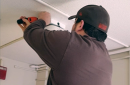 Photo of telecom technician installing a wireless access point in a dorm room