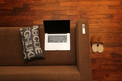 picture of a silver laptop sitting on a brown couch with a remote control on the arm of the couch, a pillow with letters next to it, and a pair of sheepskin slippers on a wood floor