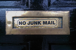 Photo of a sign that reads No Junk Mail attached to a black door