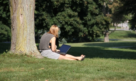 student using technology on the lawn