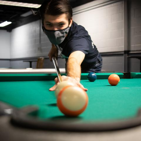 student playing billiards in the MUB gamesroom