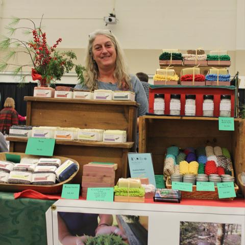 Woman standing behind booth with homemade soap