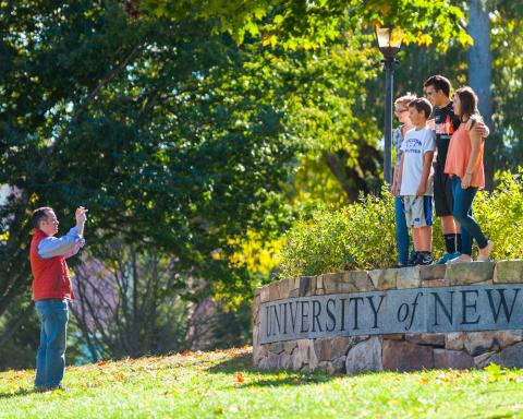 Family posing for picture on UNH campus