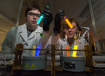 Researchers in lab with glowing test tubes