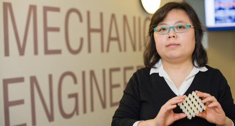 Mechanical engineering professor Yaning Li holding 3D printed square