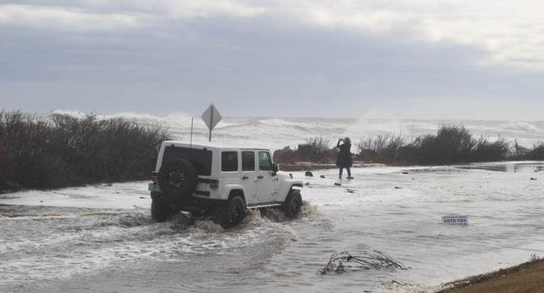 White jeep driving through flood water along coast