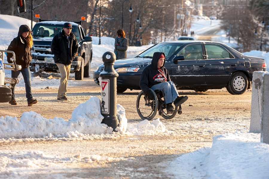 A photo of a wheelchair user in the snow