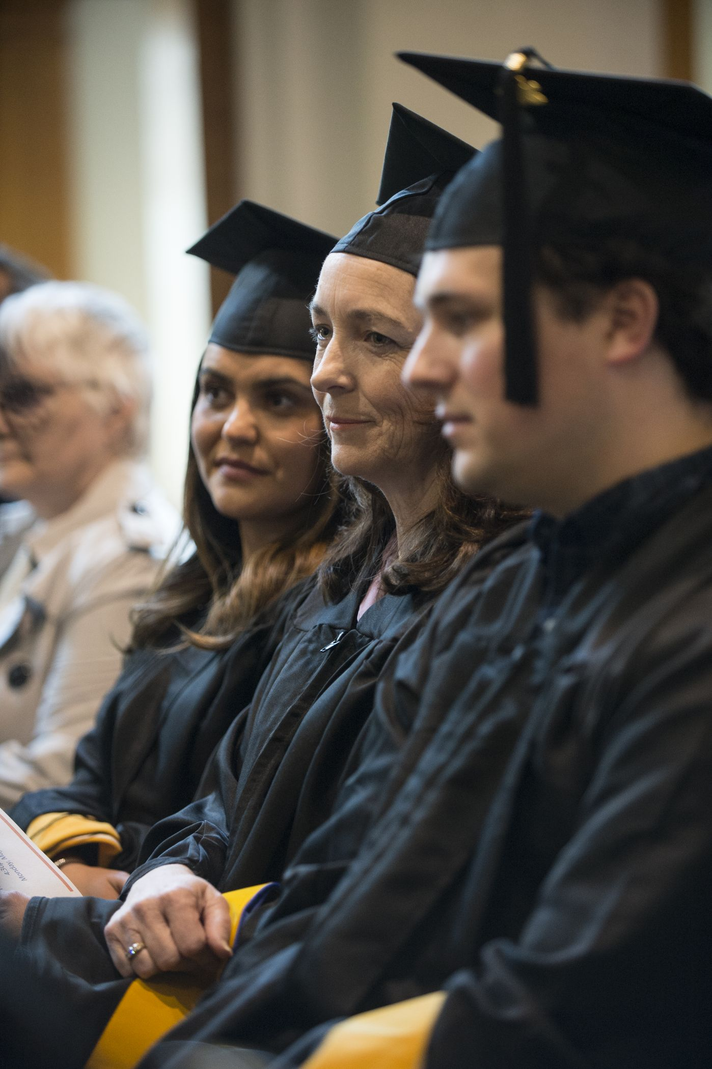 Three UNH MS students in graduation gowns sitting at their commencement