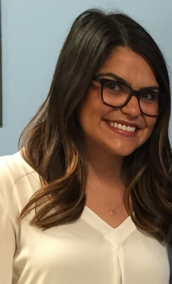 head shot of female student with brown hair, wearing black-framed glasses and a cream colored blouse