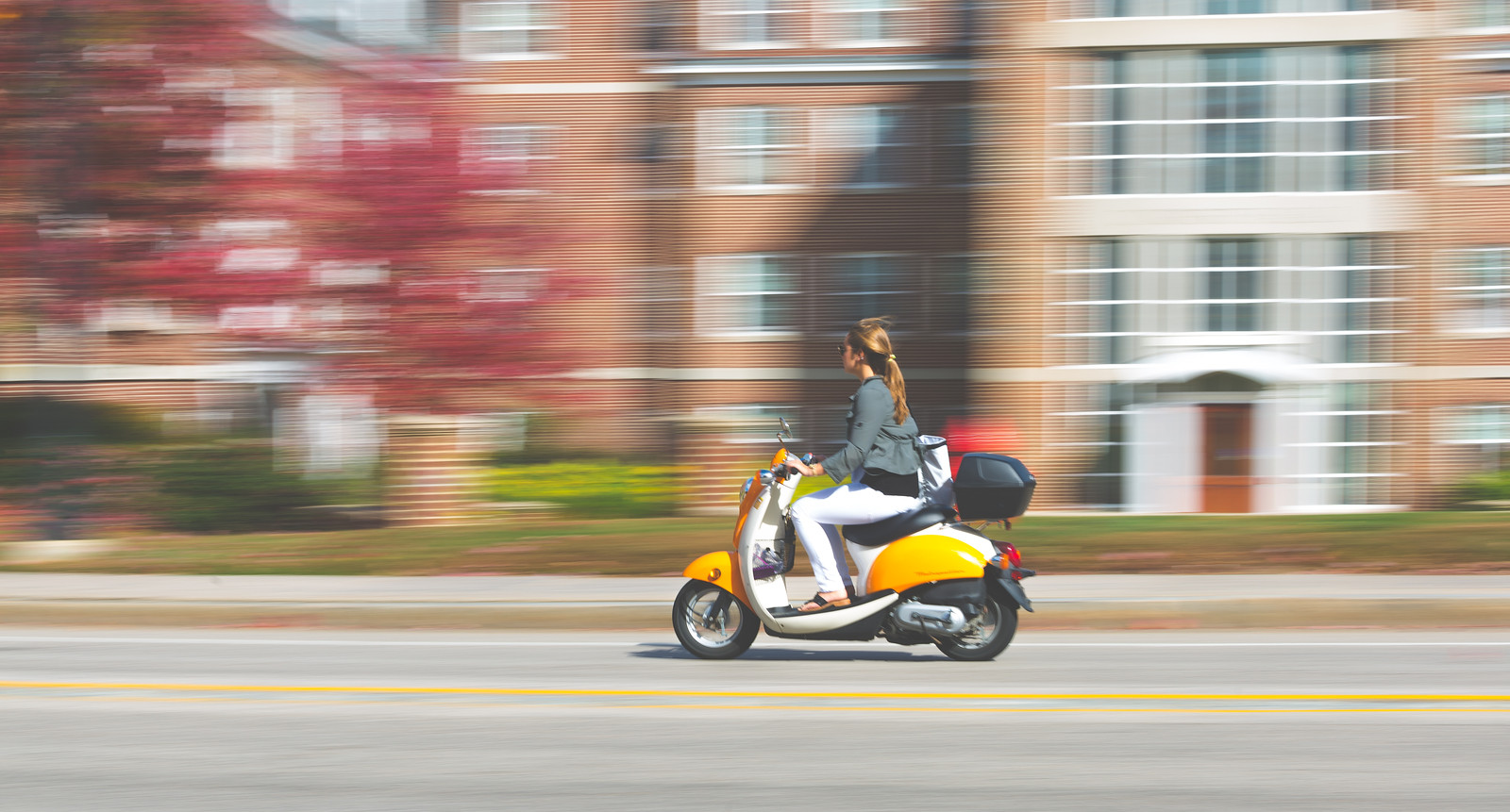 Image of student on moped driving on campus