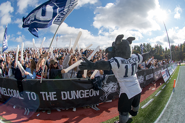 UNH mascot Wild E. Cat gets the crowd riled up at a Homecoming Weekend football game.