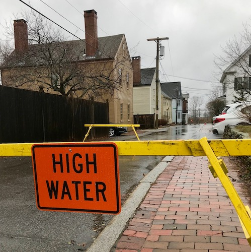 "Orange sign says ""high water"" blocking flooded street"